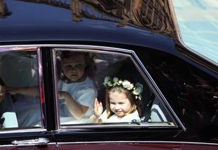 Princess Charlotte waves to the crowd as she rides in a car to the wedding of Prince Harry and Meghan Markle