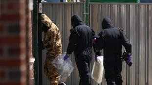 Investigators in chemical suits work behind screens in Salisbury.