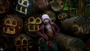 A child waits to unload drums of diesel at a jetty in the Niger Delta