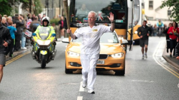 Simon Clegg carries the Olympic flame
