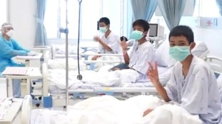 Rescued boys wave in quarantine as new Thailand cave footage shows perilous route they took to safety