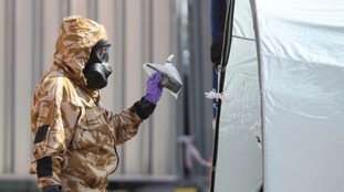 An investigator in a chemical suit works behind screens erected in Rollestone Street, Salisbury, where Dawn Sturgess lived.