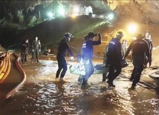 Rescuers hold an evacuated boy inside the Tham Luang Nang Non cave in Thailand