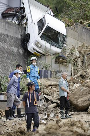 Family members watch a search operation at the site of a landslide in Kumano town, Hiroshima prefecture