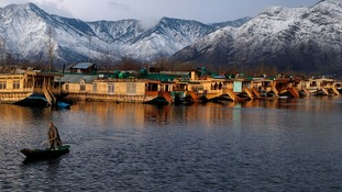 A Kashmiri man rows his boat in the waters of the Dal Lake on a cold winter evening in Srinagar