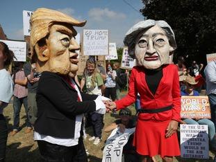 Protestors wearing Donald Trump and Theresa May paper mache heads.