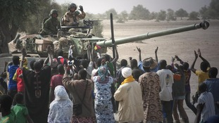 French troops aboard a tank are greeted by Malians as they arrived in Timbuktu in January