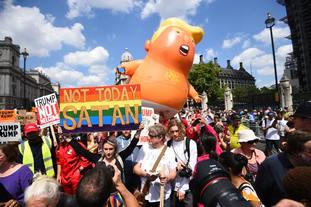 Trump Baby balloon seen in the background behind protesters including one carrying the sign