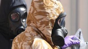 Investigators in chemical suits work behind screens erected in Rollestone Street, Salisbury.