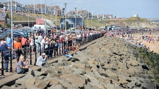 Crowds line the sea front as the tall ships depart.