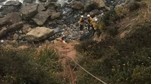 A view of rescue workers helping the injured woman at the bottom of the cliff