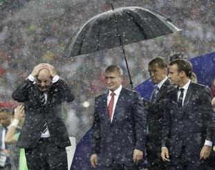 Vladimir Putin stands underneath an umbrella watched by French President Emmanuel Macron after the final match between France and Croatia at the 2018 World Cup