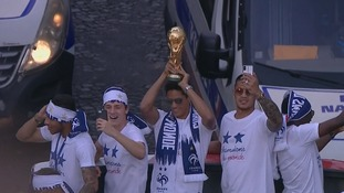 Raphaël Varane holds aloft the World Cup trophy at the victory parade.