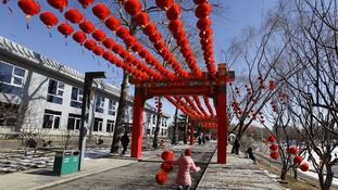 A girl holding red lanterns used for decoration runs in a park ahead of Chinese New Year celebrations.