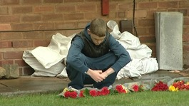 Ethan's friend lays flowers at his home in Sheldon