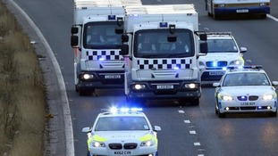 Police vans thought to be carrying at least one of the defendants in the Dale Cregan trial drive along the M61 in Bolton.