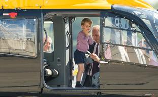 Prince George stands in a rescue helicopter as his father the Duke of Cambridge adjusts a helmet for him to wear, during a visit to Airbus in Hamburg, Germany with the Duchess of Cambridge and sister Princess Charlotte