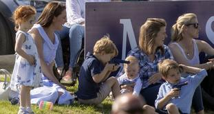 Prince George plays with a toy gun as he sits with his mother the Duchess of Cambridge (left), whilst his father the Duke of Cambridge takes part in the Maserati Royal Charity Polo Trophy at the Beaufort Polo Club, Downfarm House, Westonbirt, Tetbury