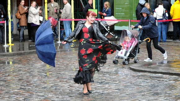 reet entertainer Dolores Delight entertains crowds queuing in the rain in London's Covent Garden, on a wet Bank Holiday Monday.