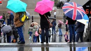 Visitors armed with umbrellas in Trafalgar Square, London.