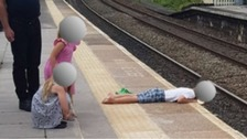 Boy seen lying with head over train platform edge