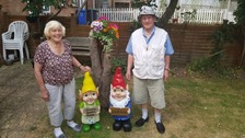 The elderly couple with their replacement gnomes.