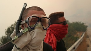 A local wears a snorkel amid the smoke.
