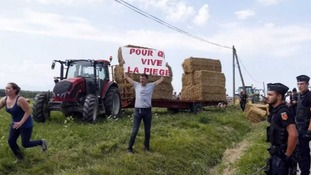Farmers protesting with tractors and hay causing disruption to stage 16 of the Tour de France