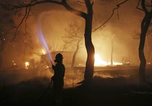 A firefighter sprays water on the fire in the town of Mati, east of Athens
