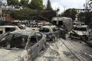People stand amid the charred remains of cars in Mati.