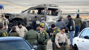 Law enforcement officers in front the truck identified as belonging to ex-LAPD officer Christopher Dorner as it is towed