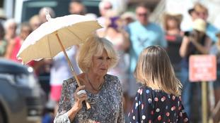 Duchess of Cornwall keeps cool under a parasol as temperatures soar at flower show