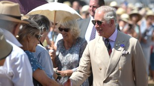 Camilla sheltered under a parasol in the scorching temperatures.
