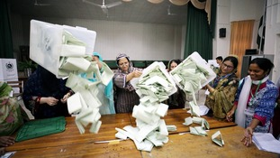 Election officials open ballot boxes to begin counting votes in Islamabad.