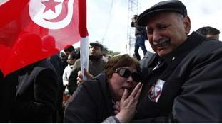 A couple mourns during the funeral procession for the late secular opposition leader Chokri Belaid