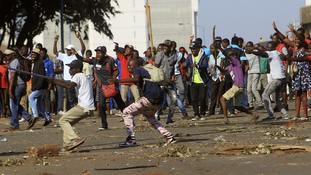 Opposition party supporters react after police fired tear gas in Harare.