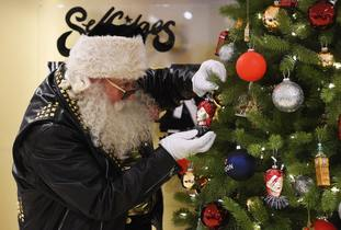 Santa places a David Bowie bauble on a Christmas tree at the launch of the Selfridges Christmas shop at the flagship store on Oxford Street.