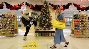 A shopper walks past Santa at the launch of the Selfridges Christmas shop at the flagship store on Oxford Street.