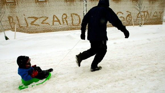 A man pulls his son in a sled in Boston, Massachusetts