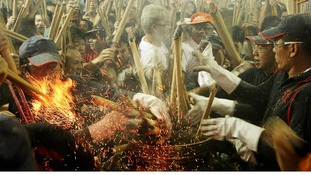 Worshippers rush to place joss sticks at the Kwan Im Thong Hood Cho temple in Singapore