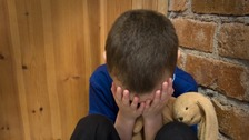 Young boy holds head in hands in corner of room