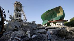 A resident inspects a mosque damaged by an earthquake in North Lombok, Indonesia.