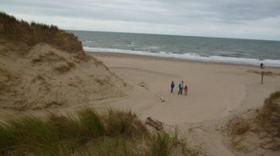 Sand dunes and people on beach