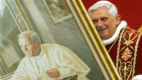 Pope Benedict XVI&#x27;s holds a portrait of the late Pope John Paul II.