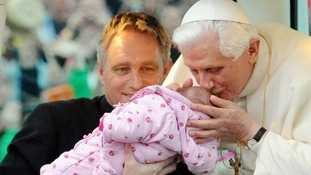 Pope Benedict XVI blessing a baby as he arrives in Hyde Park for a Prayer Vigil.