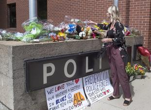Flowers are placed outside the police station in Fredericton