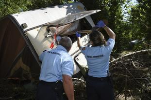 Gendarmes inspect a damaged caravan