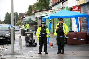 Police officers stand at the cordoned off area in Claremont Road, Moss Side