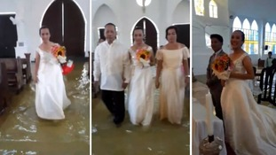 Here comes the tide! But smiling bride refuses to be put off as she wades her way down the aisle