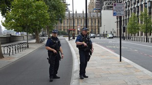 Armed police stand guard in Westminster.
